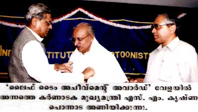 Honorable Chief Minister of Karnataka Shri SM Krishna honors Yesudasan with 'Life Time Avhievement Award' of Indian Institue of Cartoonists' on June 09, 2001.